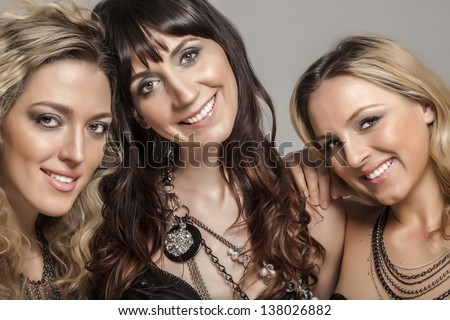 Three charming young women on grey background