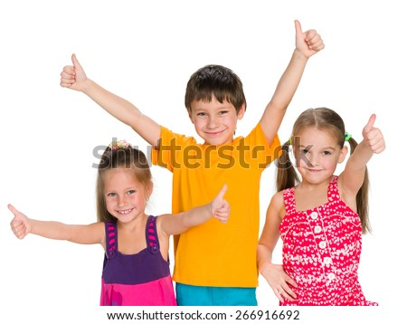 Three cheerful children holding their thumbs up on the white background - stock photo