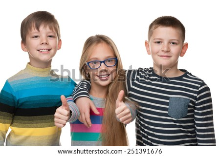 Three cheerful children stand together on the white background - stock photo