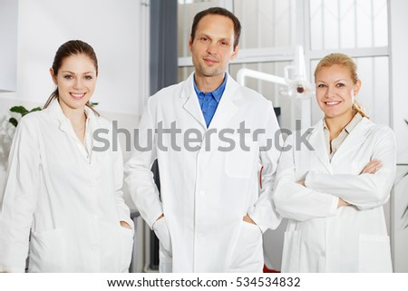 Three cheerful dentists standing in the office.
