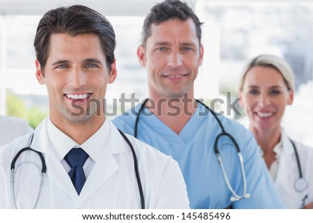 Three cheerful doctors standing in a bright hospital - stock photo