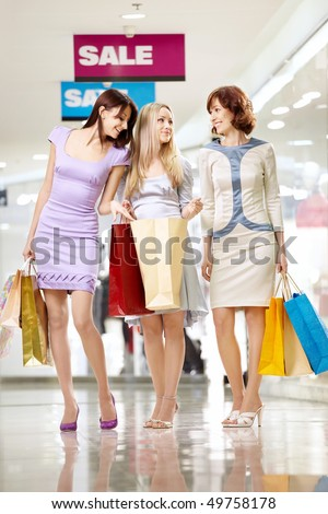 Three cheerful girl-friends with bags on walk in shop - stock photo