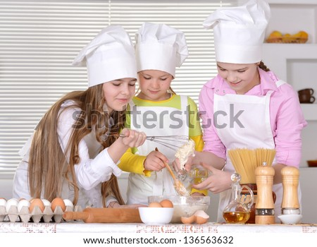 Three cheerful girls baking a cake in the kitchen together - stock photo
