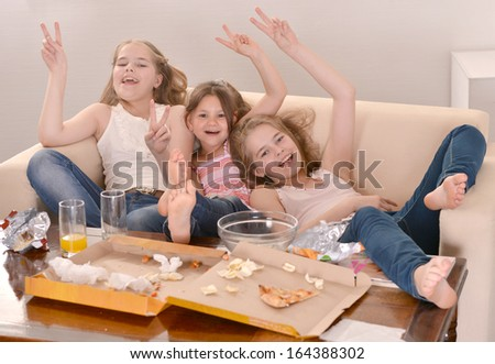 Three cheerful girls watching television together - stock photo
