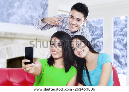 Three cheerful young people using a smartphone to take self picture at home in winter day - stock photo
