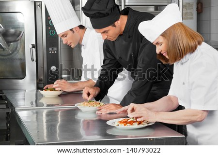 Three chefs garnishing dishes on commercial kitchen counter - stock photo