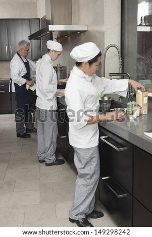 Three chefs working together in busy commercial kitchen - stock photo