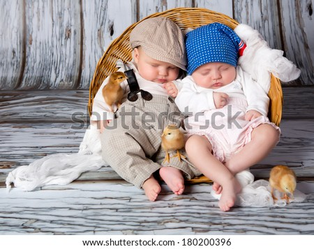 Three chicks and a cute sleeping little newborns baby in wicker basket. - stock photo