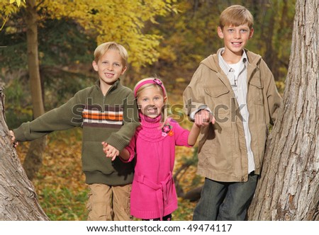 three children holding hands among the fall trees in autumn - stock photo