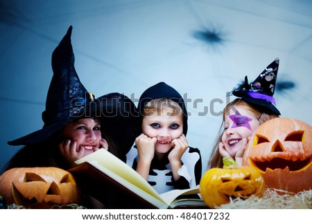 Three children in Halloween costumes reading a book among pumpkins, looking at camera and smiling