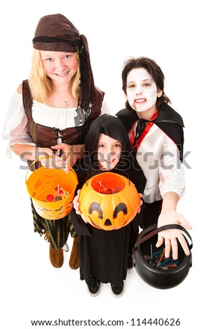 Three children in Halloween costumes, trick or treating.  Full body isolated on white. - stock photo
