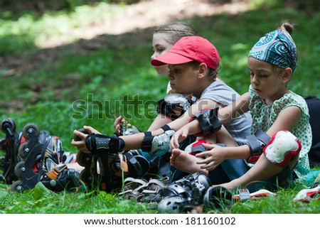 Three children in rollerblades sitting on grass in park after skating - stock photo