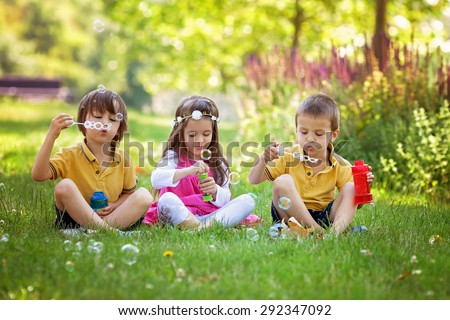 Three children in the park blowing soap bubbles and having fun, summer sunny day