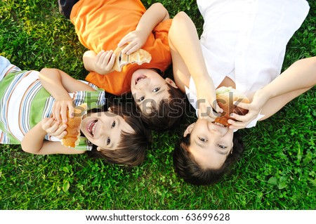 Three children laying on green grass on ground and eating sandwiches and smiling, healthy food, good friendship and love and happiness without limit :) - stock photo