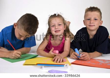 Three children lying on the floor coloring on bright colored paper.