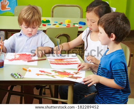 Three children painting with watercolor on paper in a kindergarten
