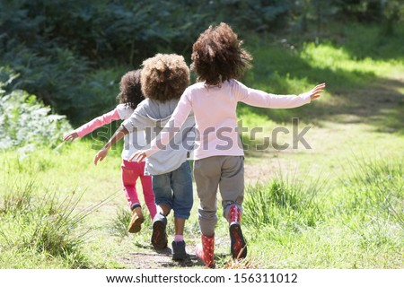 Three Children Playing In Woods Together - stock photo