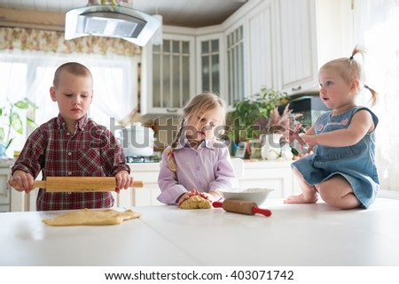 three children preparing cookies in the kitchen, siblings, large family. casual lifestyle photo series in real life interior - stock photo