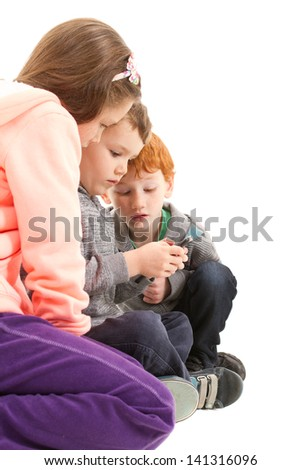 Three children sending sms on mobile phone. On white. - stock photo