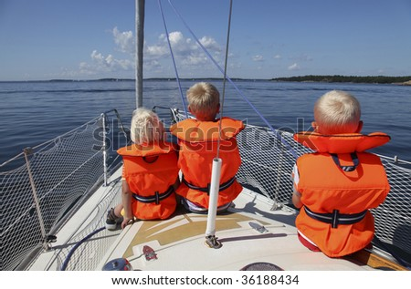 Three children sitting in the front of an sailboat wearing life-jackets