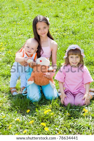 Three children sitting on the grass in the sun - stock photo