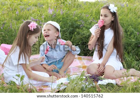 Three children sitting on the rug in the grass and eat lollipops outdoors