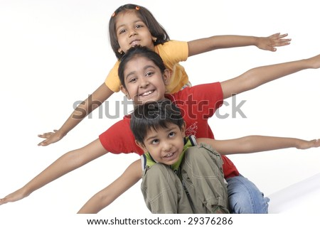 three children sitting with arms outwards - stock photo