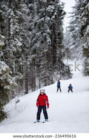 Three children skiing down the ski slope - stock photo