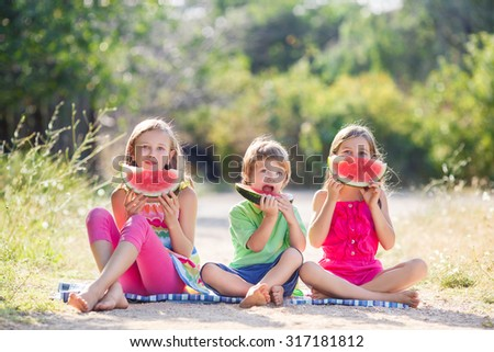 three children summer portrait. smiling children outdoor. children with watermelon. Three happy smiling child eating watermelon in park. Group of happy kids eating watermelon on grass in summer park