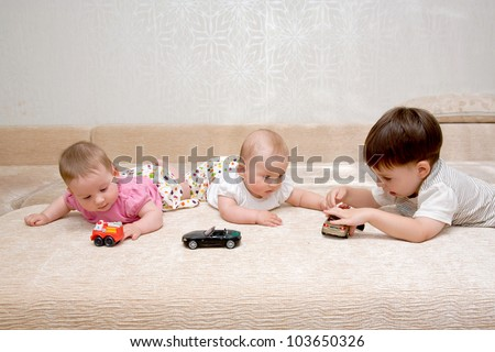 Three children - two tiny twin sisters baby girls and their older brother on the sofa playing with toy cars. Happy childhood. - stock photo