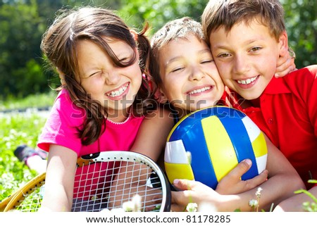 Three children with sports equipment embracing, looking at camera and smiling - stock photo