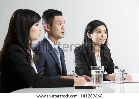Three Chinese Business people meeting in office to discuss a project. Shallow Depth-of-field used to focus on one employee
