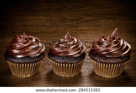 Three chocolate cupcakes in a row over a wooden background - stock photo