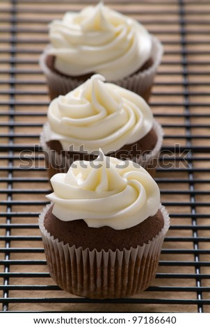 Three chocolate cupcakes with vanilla frosting in a row - stock photo