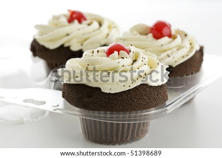 Three chocolate cupcakes with white frosting and red cherry - stock photo