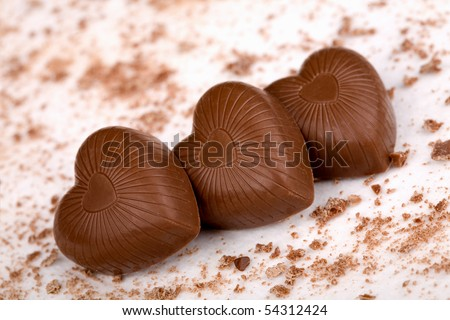 Three chocolate hearts with crumbs on white background - stock photo