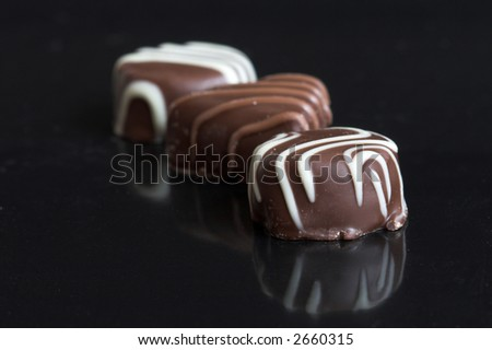 Three chocolates in a row on black background with reflection - stock photo