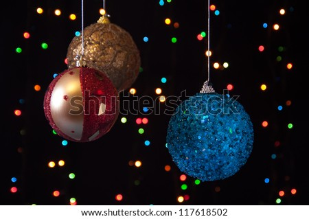 three Christmas ball on a black background with lights