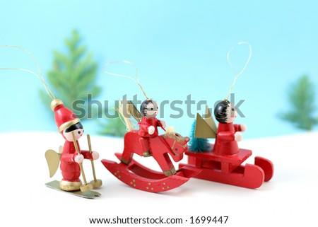 Three Christmas tree decorations set off across a snowy landscape - stock photo