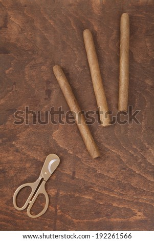 three cigars and gold scissors on the old table - stock photo
