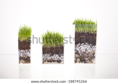 Three clear containers show a cross section of pebbles, shredded paper, dirt and grass on a glass table. - stock photo