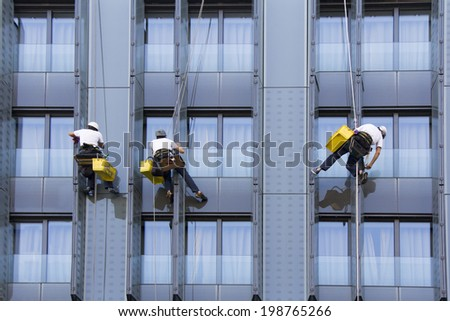 Three climbers wash windows and glass facade of the skyscraper