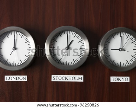 Three clocks with different time on Teak background