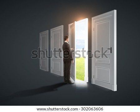 three closed doors and one opened by businessman to field - stock photo