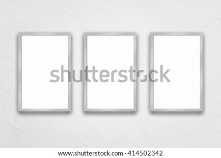 three closed up hanging blank frame on white concrete background for product presentations or portfolios