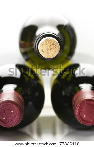 Three closed wine bottles lying on white background. - stock photo