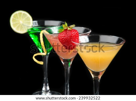 Three cocktails cosmopolitan cocktails decorated with citrus lemon twist yellow martini drink with strawberry isolated on a black background - stock photo