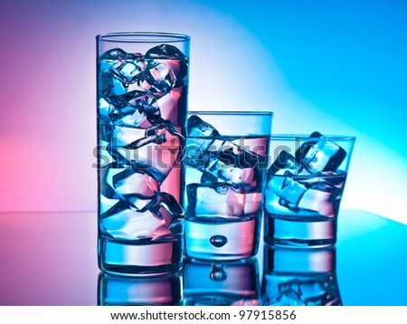 Three cocktails in different glasses on pink and blue background - stock photo