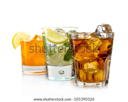 Three cocktails with orange juice, soda, lemon, mint and coke