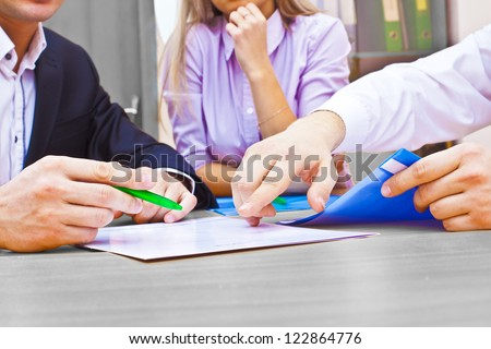 Three colleagues are discussing a table yours business plans - stock photo